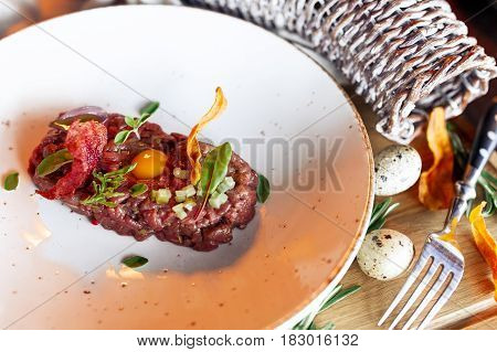 Veal tartar with quail eggs over rustik background