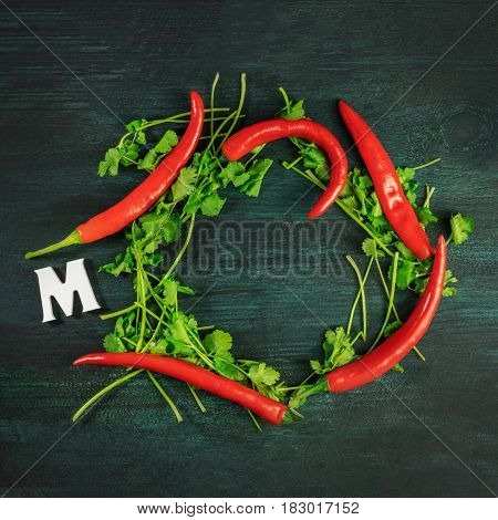 A square photo of a wreath of cilantro leaves with red hot chili peppers, letter M for Mexico, and a place for text