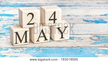 May 24th. Wooden cubes with date of 24 May on old blue wooden background.