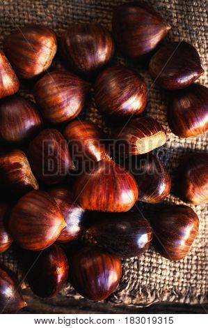 Raw Chestnuts on old wooden table with copy space close up. Beautiful chestnuts top view