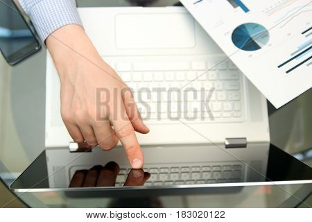 Business man working and analyzing financial figures on a graphs using laptop