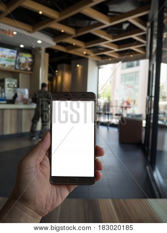 Man hand holding touch screen smart phone with white blank empty screen (ISOLATED) blurred fast food restaurant for background.