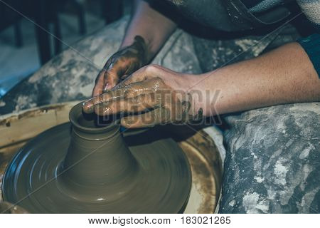 Pottery making, dirty hands in wet clay, apron, pottery wheel, close up of craftsperson. Ceramic handmade in workshop