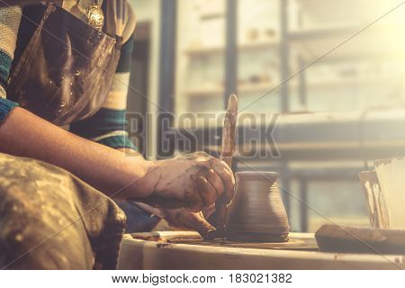 Young woman potter in apron at work. Craftsman artist shapes the jug with his hands and a special tool on pottery wheel. Copy space, toned