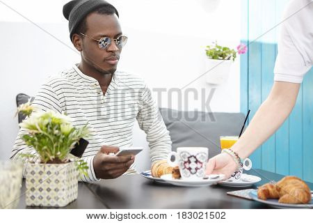 Unrecognizable Waiter With Plate In Hand Serving Stylish Dark-skinned Male Guest Table At Restaurant