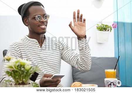Cheerful Friendly-looking Young African American Man Wearing Trendy Headwear And Sunglasses Raising