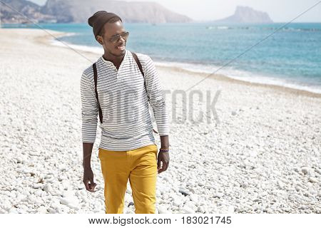Fashionable Young African American Tourist Smiling Happily Watching Dolphins Playing In Ocean During