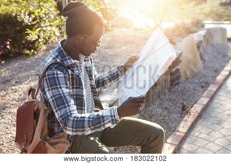 Portrait Of Young Stylish African Traveler Sitting On Roadside Stones Examining Attentively Paper Ma