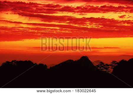 A dramatic sunrise over the silhouette of mountains on the Yellow Mountain (Huangshan) range in Anhui Province China on a beautiful morning.