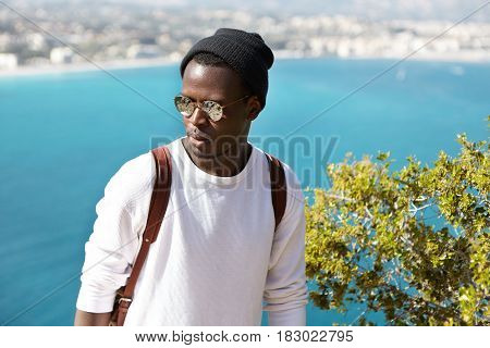 Headshot Of Serious African Man Against Background Of Picturesque View Of European Seaport Town. Tra