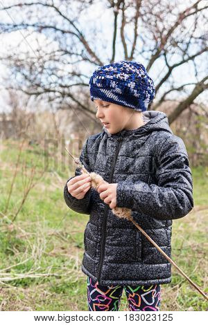 Girl in a blue jacket and beret clean the bulrush