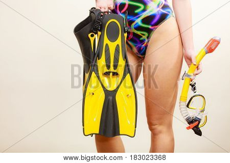 Female slim fit body wearing colorful swimsuit with mask tuba flippers and snorkel studio shot on grey. Girl preparing to summer vacation. Snorkeling gear swimming concept.