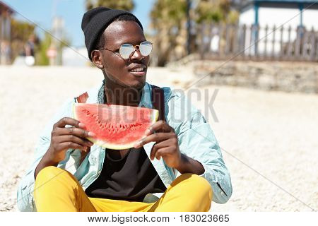 Outdoor Summer Shot Of Handsome Dark-skinned Man In Trendy Clothes And Eyewear Relaxing On Beach At