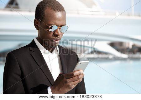 Handsome Young African American Office Worker In Elegant Black Suit And Eyewear Standing In Urban Su