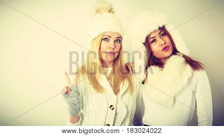 Two Girls In Warm Winter Clothing Having Fun.
