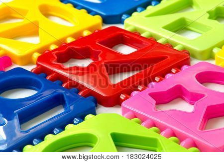 Background of multi-colored plastic puzzle elements. View at an angle. Early development of children. The study of geometric shapes.