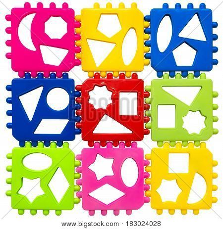 Multicolored plastic puzzles on a white background. View from above. Early development of children. The study of geometric shapes.
