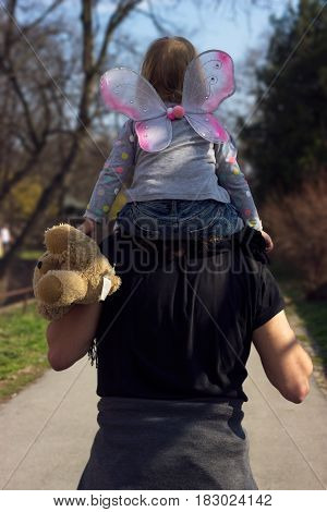 Father carrying little toddler girl with butterfly wings and teddy bear on his shoulders