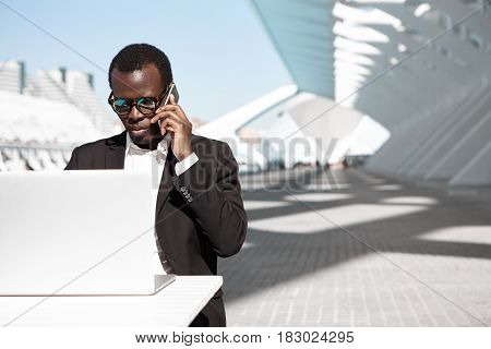 Outdoor Portrait Of Successful Confident Young African Entrepreneur Or Corporate Worker In Black Sui