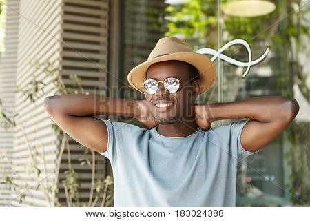 Happy And Relaxed Young Dark-skinned Male Student In Stylish Sunglasses And Headwear Keeping Hands B