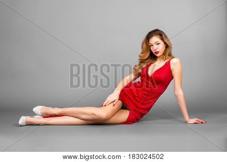 Fashionable pretty sexy young blonde woman posing on gray wall background
