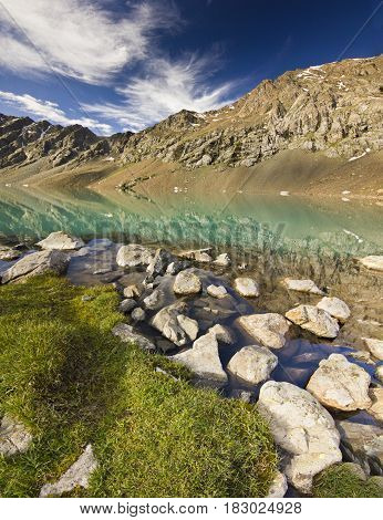 blue calm mountain lake Alakol with stones on shore and clouds on blue sky in tian-shan mountains at sunrise
