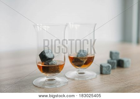 Grey stones cubes for cooling whiskey and glases tulip on light wooden background