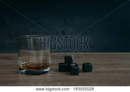Grey stones cubes for cooling whiskey and glases tumbler on dark wooden background