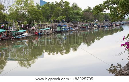 Long tail boats and fishing boats in the canal at phuket Thailand