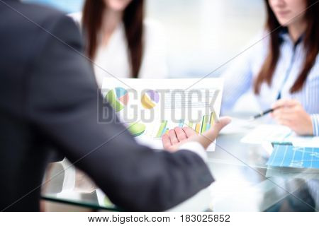 Young businessman hand pointing at graph document during discussion at meeting.