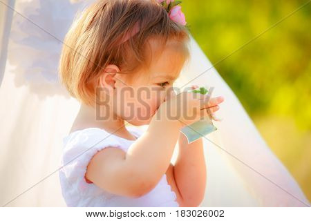 Little beautiful girl in a white dress drinks from a cup. The girl on the background of the tent holds a cup with handle rejected aside finger. A child's birthday is on the street.