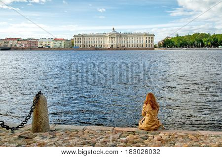Woman in cloak sits with his back, on stone embankment looks at the river Neva in Saint-Petersburg