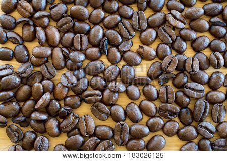 Coffee beans on wooden table - background