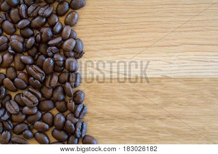 Coffee beans on wooden table. Empty space or text or logo.