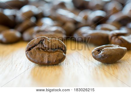 Coffee beans on wooden table closeup. Shallow depth of field.