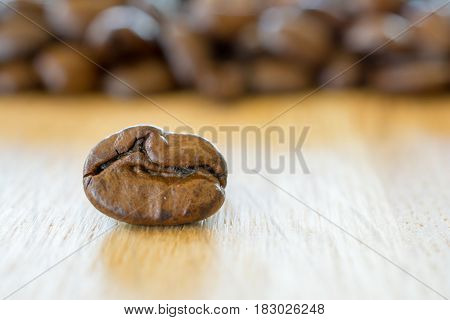 Coffee bean on wooden table closeup. Shallow depth of field.