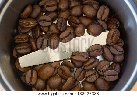 Coffee beans inside coffee grinder closeup - background