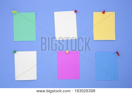 colorful paper note with pin on blue paper background