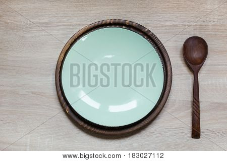 Elegance table set with turquoise plate on wooden table-top. Rustic stile. Top view. Image with copy space.