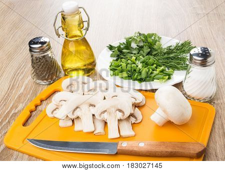 Slices Of Mushrooms On Cutting Board, Pepper, Salt, Oil, Greens