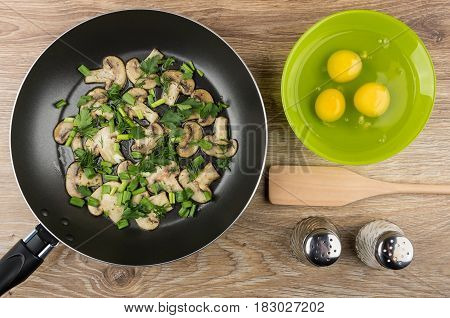 Fried Mushrooms With Greens In Frying Pan, Raw Eggs