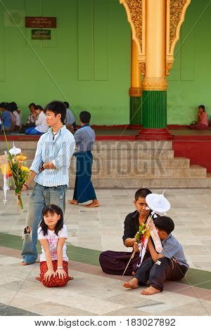 Yangon Myanmar January 01 2007 - Burmese people with ritual offering waiting for a ceremony at famous Buddhist temple at Yangon city - pagoda Shwedagon.