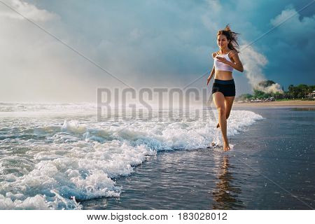 Active sporty woman run along ocean surf by water pool to keep fit and health. Sunset black sand beach background with sun. Woman fitness jogging training and sport activity on summer family holiday.