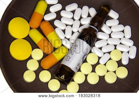 Yellow and white pills yellow capsules and brown ampoule with medicine on a brown plate