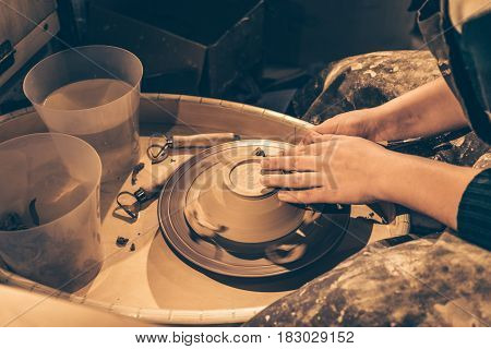 Potter in workshop, potter wheel with clay pot and craftswoman with tools in hands, toned photo