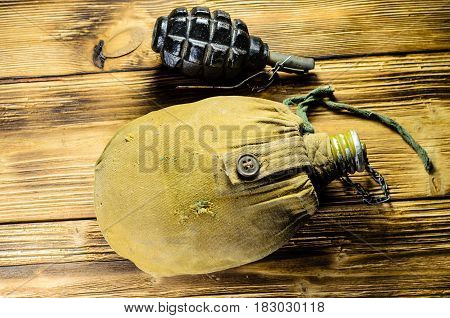 Army Flask And Hand Grenade On Wooden Table