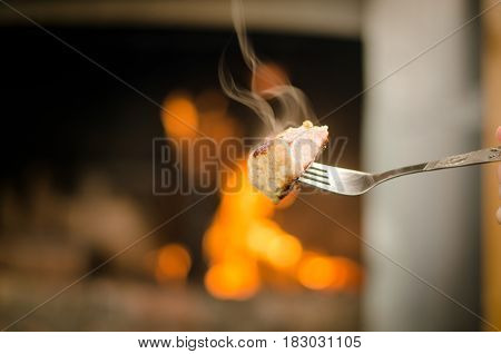 Smoky barbeque grilled meat on the fork. Meat on the coals with blurred bonfire background.
