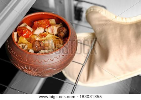 Human hand checking crock pot with chicken ragout in oven