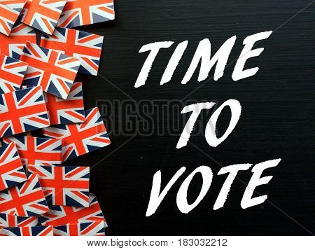 The words Time To Vote in white text on a blackboard next to Union Jack flags as a reminder to vote in the United Kingdom General Election