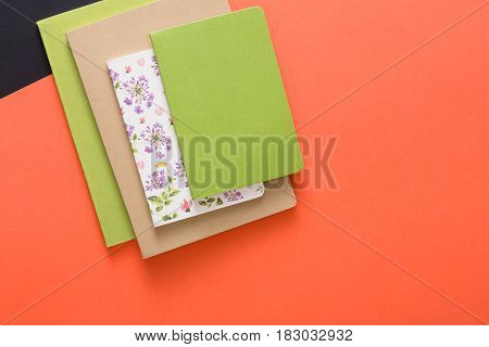 Stylish mockup with set of various colorful notebooks on creative multicolored work space background, copy space, flat lay, concept of start-up and stationery supplies